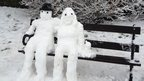 Two snowmen on a park bench