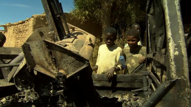 Children rest on charred vehicle
