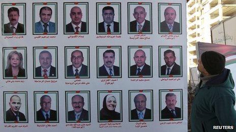 A man looks at electoral posters for parliamentary candidates in Amman January 20, 2013
