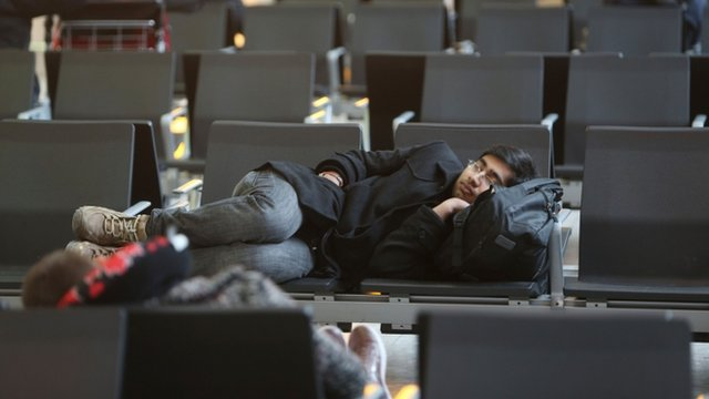 A man asleep on chairs at Terminal 5