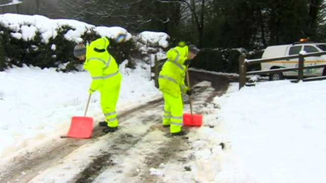 Workers clearing snow on a driveway