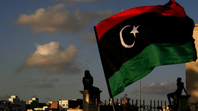 Libyan flag over Benghazi skyline