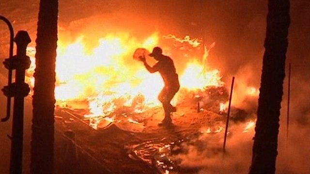 Protester pouring fuel on fire