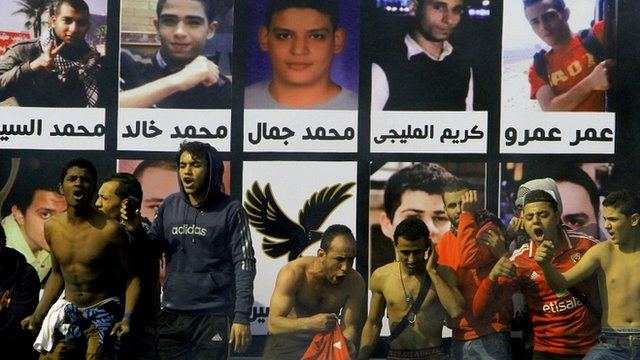 Supporters of al-Ahly club in front of pictures of victims of soccer violence at their club premises in Cairo, Egypt