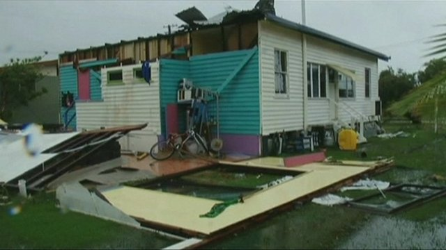 House with walls ripped away by tornado