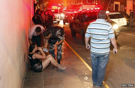A survivor is helped by emergency workers near the Kiss club in Santa Maria, Brazil, 27 January