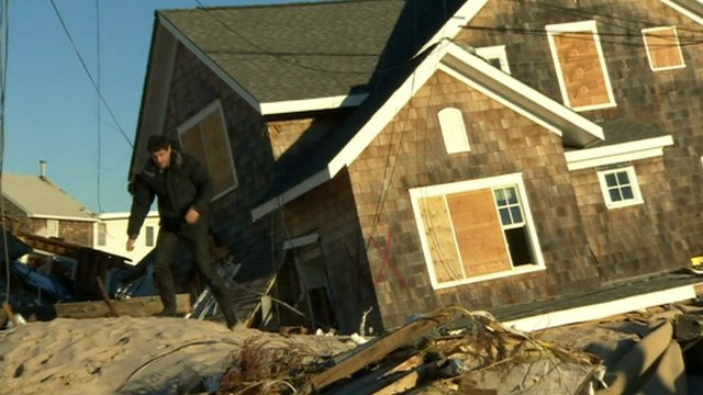 The BBC's Jon Sopel walks away from a house damaged by Sandy