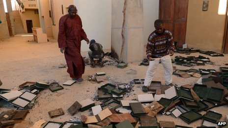 Men recover burnt ancient manuscripts at the Ahmed Baba Centre