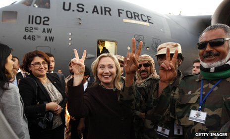 Hillary Clinton flashes the V for victory sign with Libyan fighters loyal to the National Transitional Council, 2011