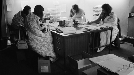 Four women working wrapped in quilts to keep warm in 1974