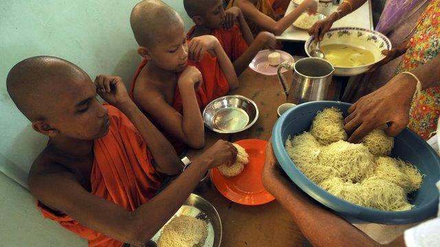 Young monks receive breakfast offerings