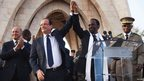 Francois Hollande (2nd L) joins hands with Mali's interim President Dioncounda Traore at Independence Plaza in Bamako, Mali, 2 February 2013