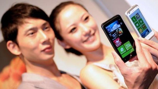 Models holding HTC phones