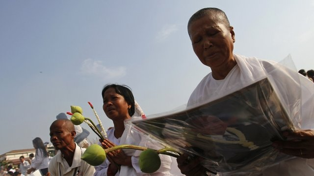 Women cry as other mourners pray at the cremations of Cambodia's former King Norodom Sihanouk