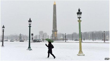 A woman walks on the snow covered Place de la Concorde, Paris