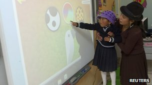 A girl of the village of Zumbahua is learning how to use a large projection touch screen at her school