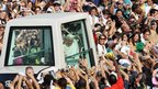 Catholic pilgrims cheer at Pope Benedict XVI as he arrives in the popemobile at the National Basilica of Aparecida, 13 May 2007