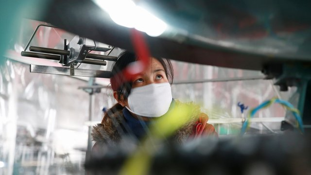A woman working in a Chinese textile factory that exports clothing to the US and Europe