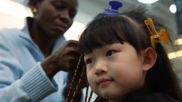 Chinese girl has her hair braided in Beijing