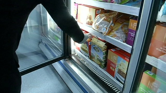 Person reaching for frozen food packet in supermarket