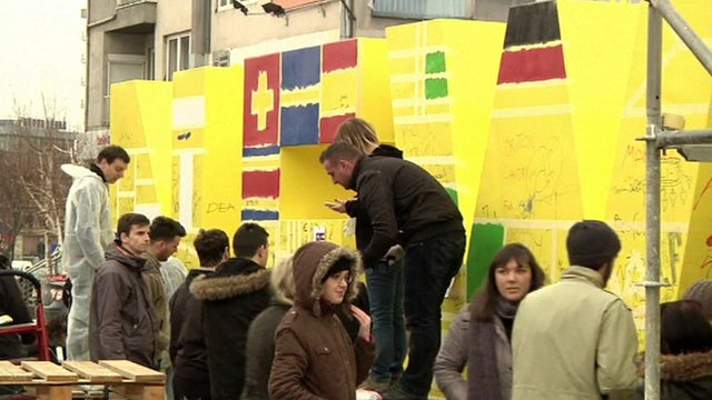 People painting flags on sculpture