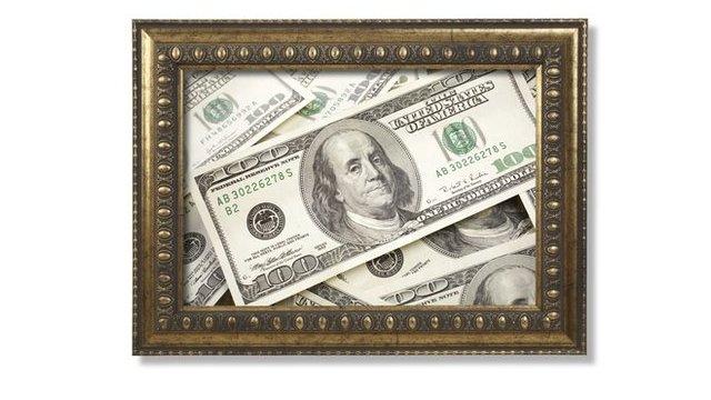 Hundred dollar bills in a brass frame