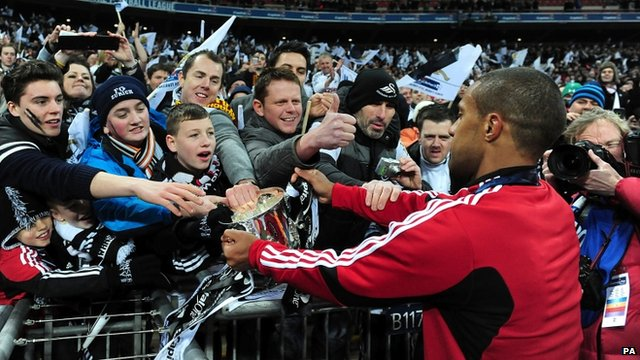 """Swansea City""""s Wayne Routledge celebrates with the Swansea fans and the Capital One Cup"""