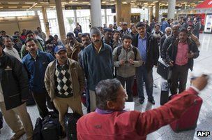 Pakistani and Indian employees of subcontracters working for British oil giant BP in Algeria listen to a man giving informations as they wait for their flight back to Dubai at the Palma de Mallorca airport on January 18, 2013.