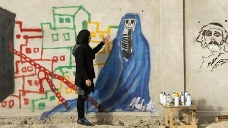 Malina Suliman in front of her drawing of a skeleton in a burka