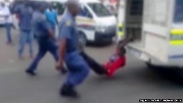 A man with his hands tethered to the back of a police vehicle is dragged behind