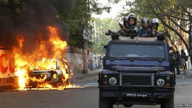 A police van passes a burnt vehicle after activists of Bangladesh Nationalist Party (BNP) set fire to it during a clash in Dhaka March 2, 2013