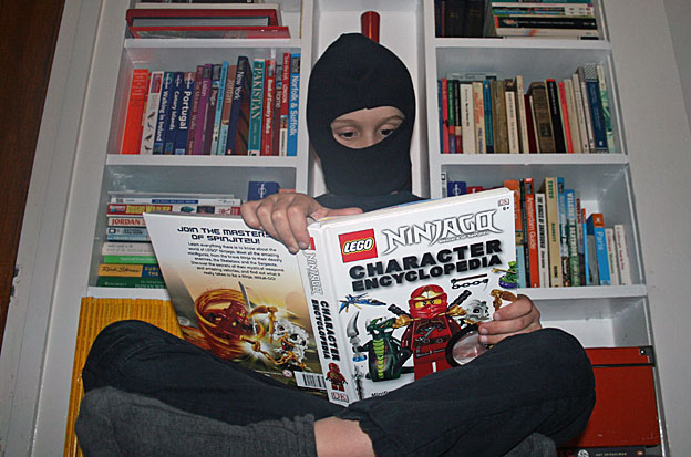 Casciani Junior reading Ninjago Character Encyclopaedia while dressed as a ninja