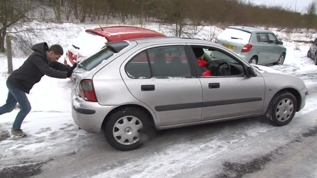 Man pushing car on snowy road