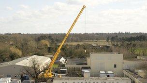 A crane lifts part of a unit into place