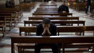 Priest prays at Jesuit Church of St Ignatius in Rome