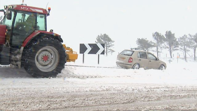 Car and tractor in snow