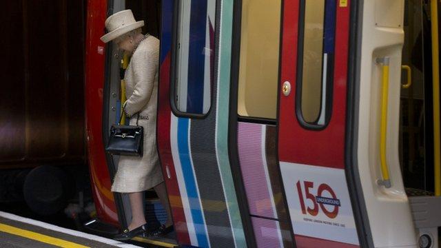 Queen Elizabeth II steps off a parked train she was shown around at Baker Street underground station