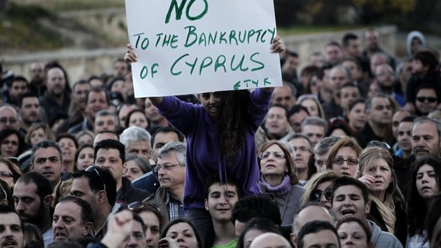 "Woman sitting on shoulders of protester, holding sign saying ""No to the bankruptcy of Cyprus"""