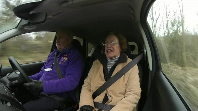 Elderly woman being driven in a car