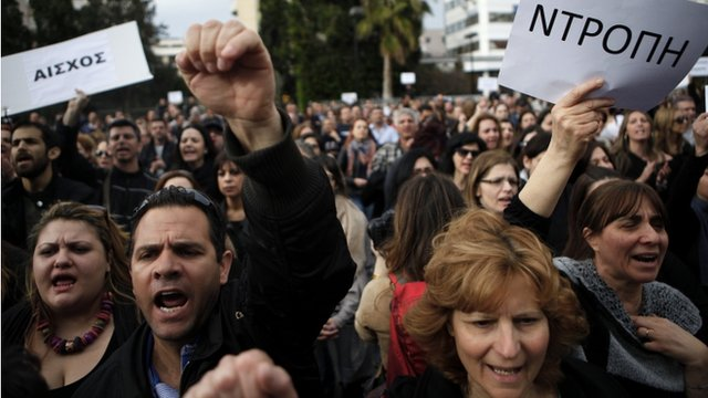 """Employees of the Bank of Cyprus shout slogans as they holds banners reading in Greek """"shame"""" during a protest at Cyprus central bank in Nicosia"""