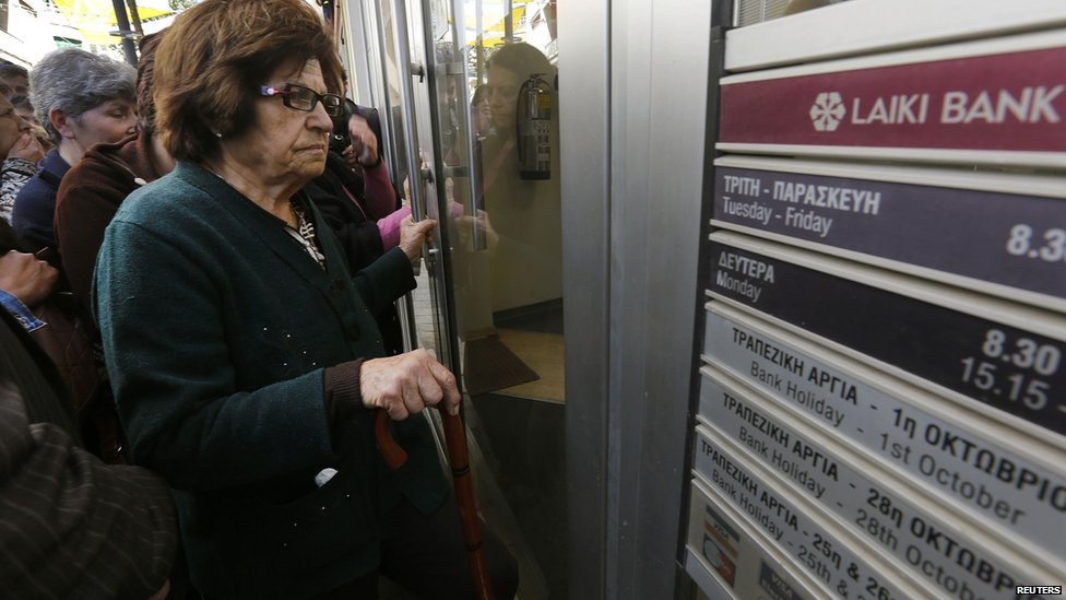 Depositors wait outside a Laiki Bank branch shortly before it opened in Nicosia 28 March 2013