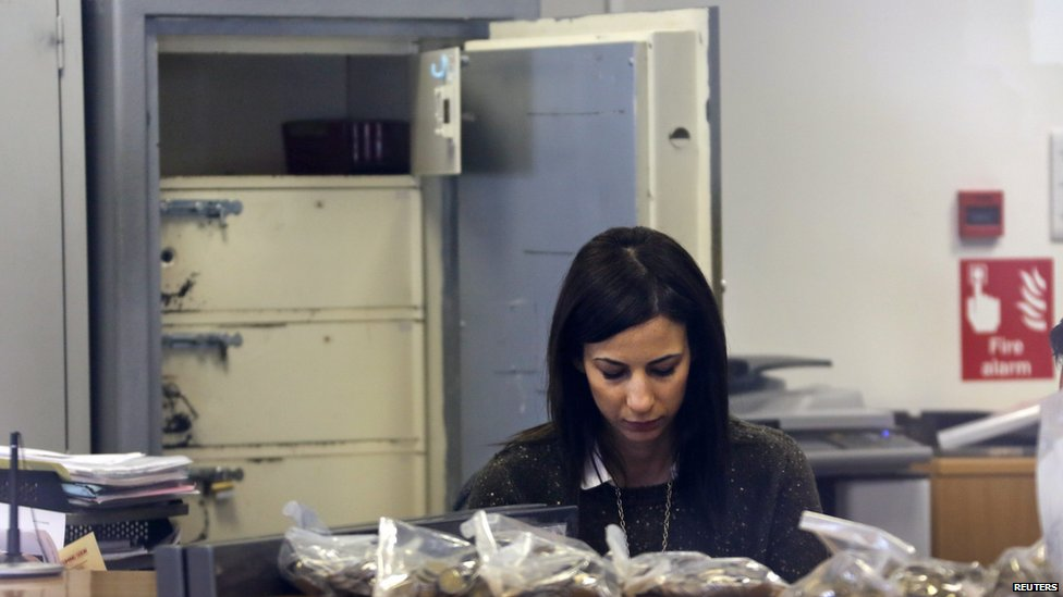An employee counts money by an open safe inside a Laiki Bank branch before it opened in Nicosia 28 March 2013