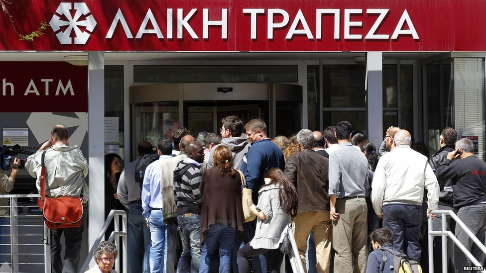 People wait to enter at a branch of Laiki Bank shortly after it opened in Nicosia March 28, 2013