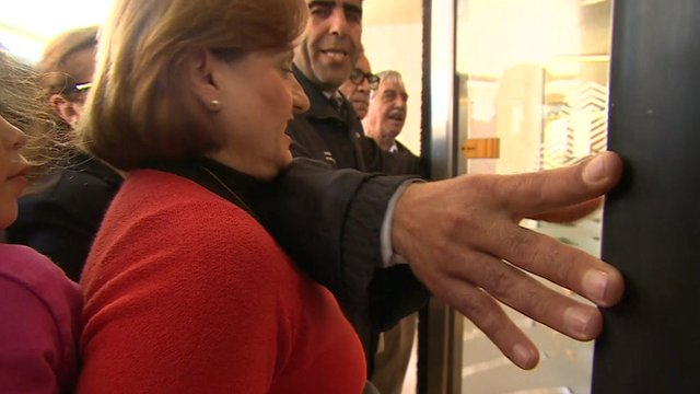 Cypriots queue to get into the reopened banks