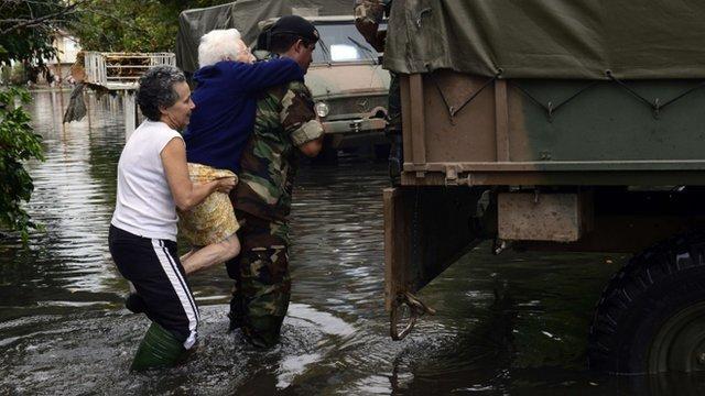 A soldier evacuates an elderly woman in a flooded street in La Plata