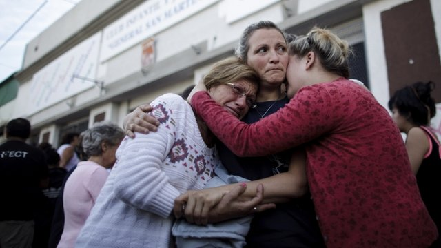 People embrace outside a club where the Red Cross set up a centre to help flood victims in La Plata
