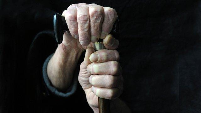 Elderly person holding onto walking stick