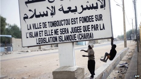 """Children playing next to a board reading """"Timbuktu is founded on Islam and will be judged by Islamic laws"""" on 31 January 2013 in Timbuktu"""