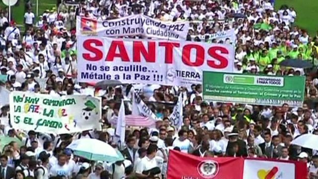 Crowds holding banners march in Colombia