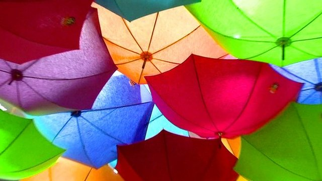 Some of Jacques Demy's colourful umbrellas hanging from a ceiling